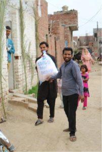 Two men with sack of aid (Edge, Pakistan)